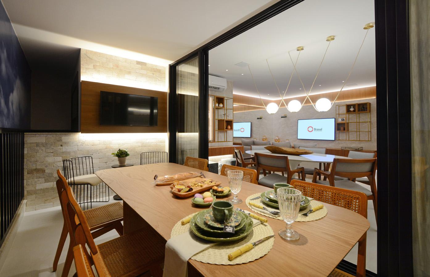 Varanda do decorado de 119 m² com parede de pedra e mesa e madeira com seis lugares - Marcus Camargo